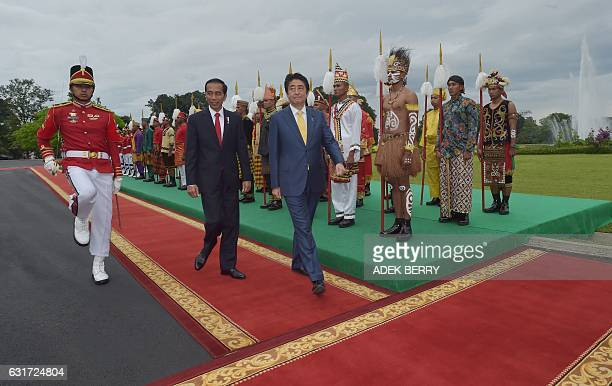 Indonesia's President Joko Widodo walks with Japan's Prime Minister Shinzo Abe as they review an honour guard at the presidential palace in Bogor on...