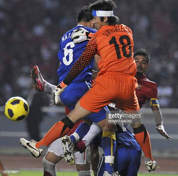 Indonesia's striker Bambang Pamungkas attempts for a goal against Thai defenders and goalkeeper Singtahweechai Hathairattanakool during their AFF...