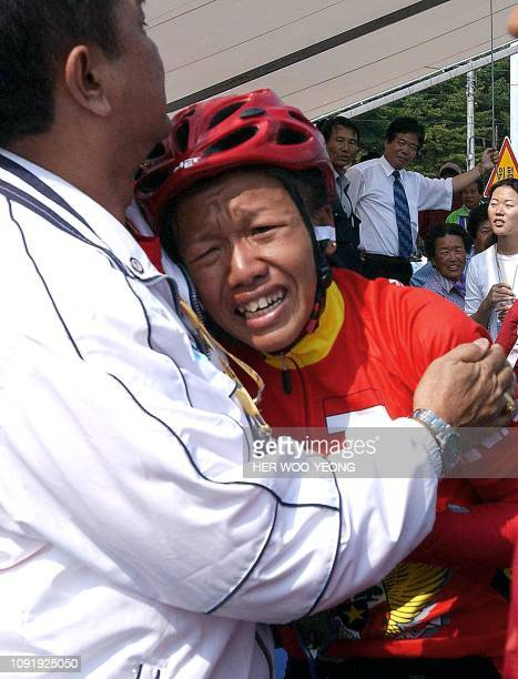 Indonesia's Uyun Muzizah cries in the arms of an Indonesian official after she came in second in the women's 968km individual road race at the 14th...