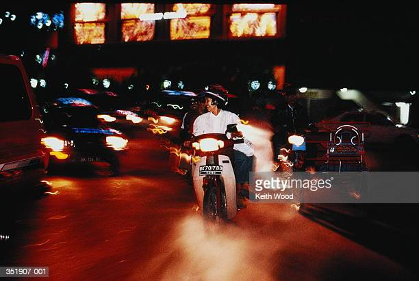 Indonesia,Sumatra,motorcyclist and cars on road at night,blurred