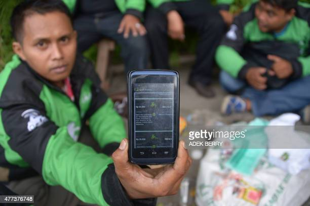 IndonesiatransporttrafficInternetFOCUS by Nick Perry This picture taken on June 11 2015 shows a motorcycle driver displaying the popular...