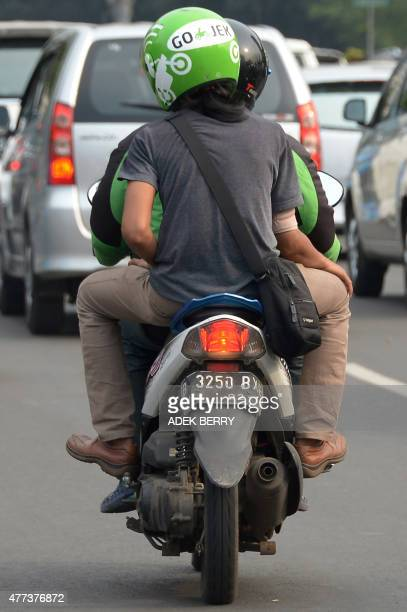 IndonesiatransporttrafficInternetFOCUS by Nick Perry This picture taken on June 11 2015 shows a motorcycle driver with Indonesian startup GoJek...
