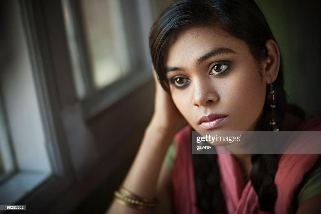 Indoor close-up of serene Asian teenager girl sitting near window. : Stock Photo