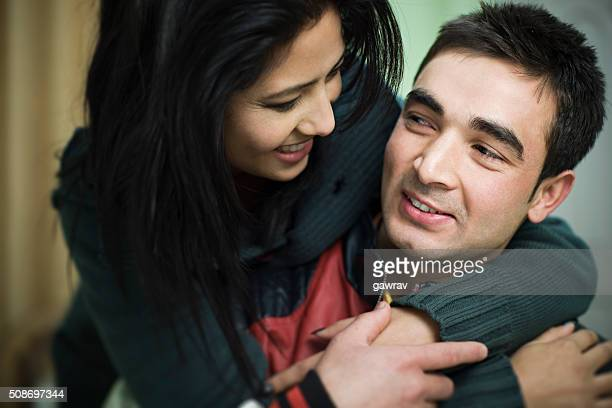 Indoor, happy and loving young couple holding each other.