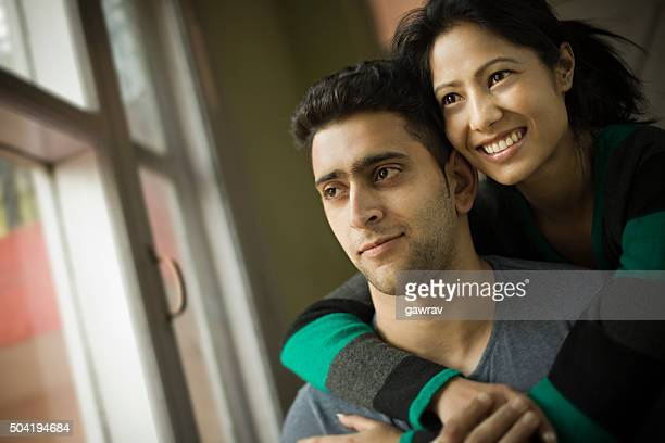 Indoor, happy young couple together looking at view outside window.