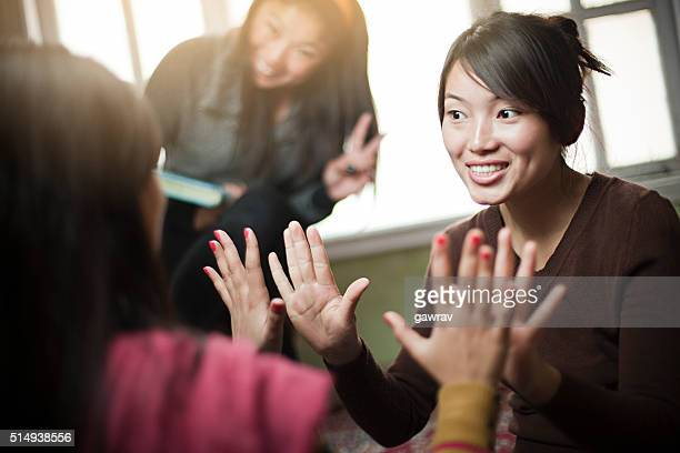 Multirracial interiores imagem de grupo de meninas a jogar Jogo de Bater Palmas.