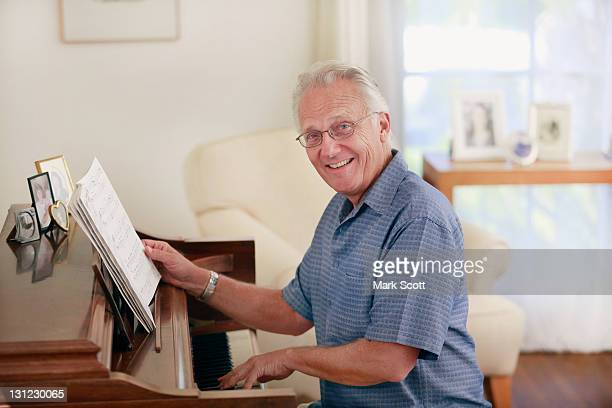 Indoor portrait of a 60 year man playing piano