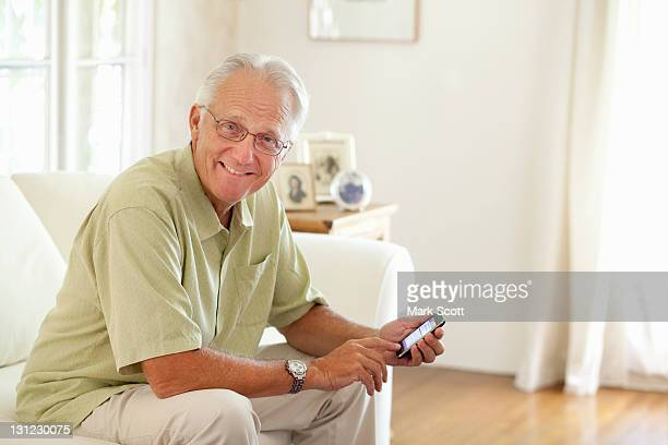 Indoor portrait of a 60 year man with smart phone