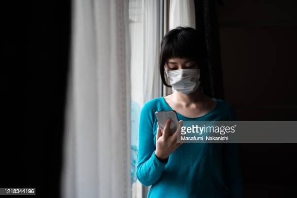 窓にスマートフォンを操作する外科マスクを身に着けているアジアの女性の屋内肖像画 - 心配する ストックフォトと画像