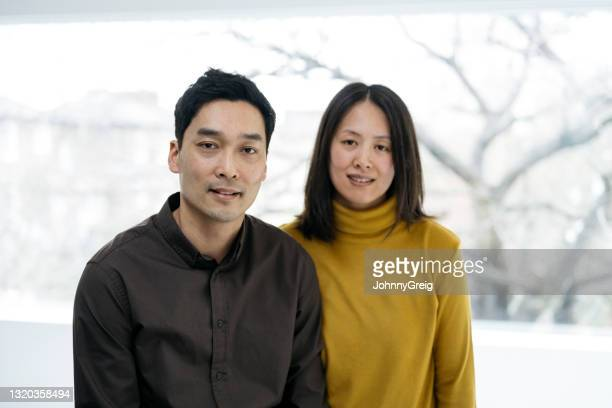 indoor portrait of chinese couple in smart casual attire - mid length hair stock pictures, royalty-free photos & images