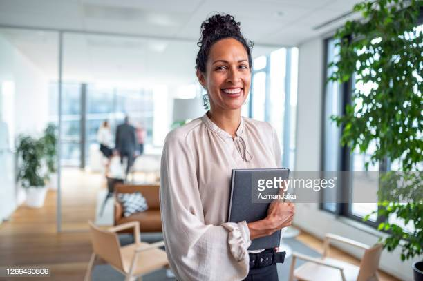 indoor portrait of smiling hispanic businesswoman in office - 40 44 years stock pictures, royalty-free photos & images