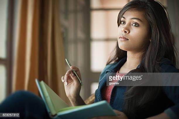 Indoor, serene Asian teenage girl student near window with book.