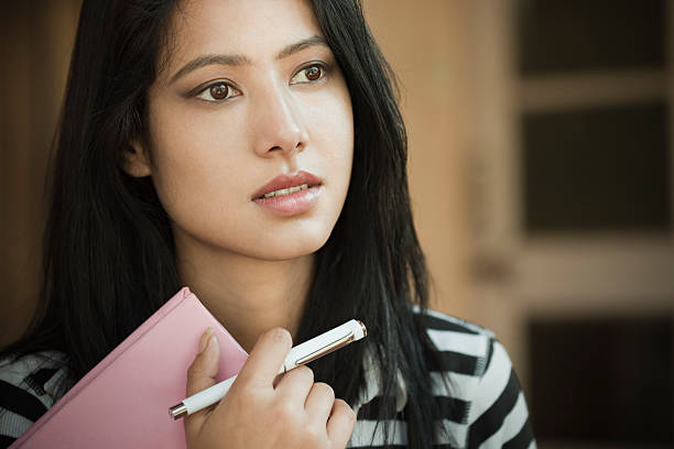 indoor, serene asian teenage girl student with book and pen. - asian teenager woman student stock pictures, royalty-free photos & images