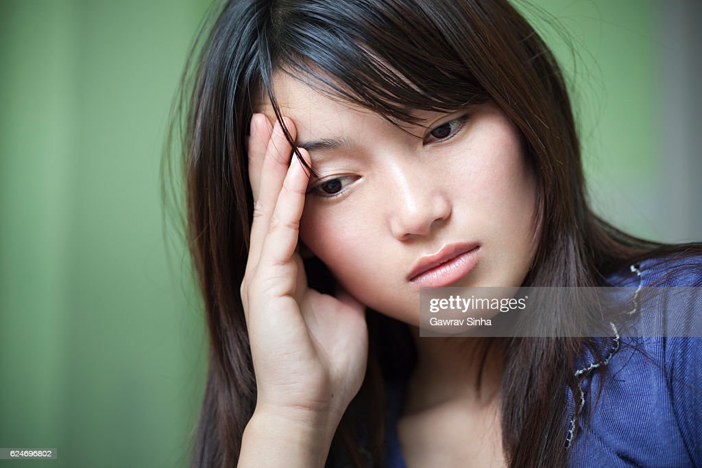 Indoor, serene, sad young woman holding head and thinking. : Stock Photo