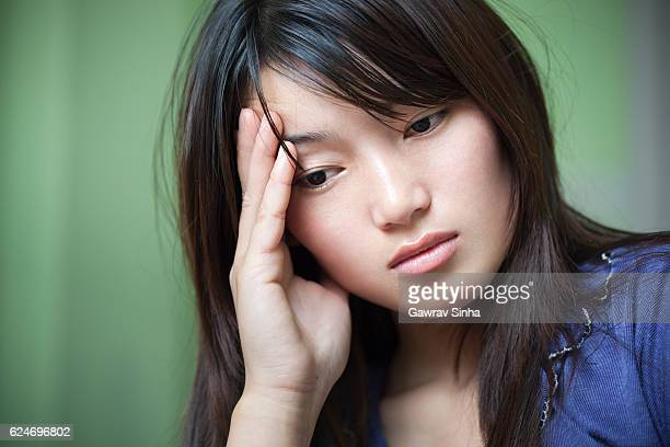 Indoor, serene, sad young woman holding head and thinking.