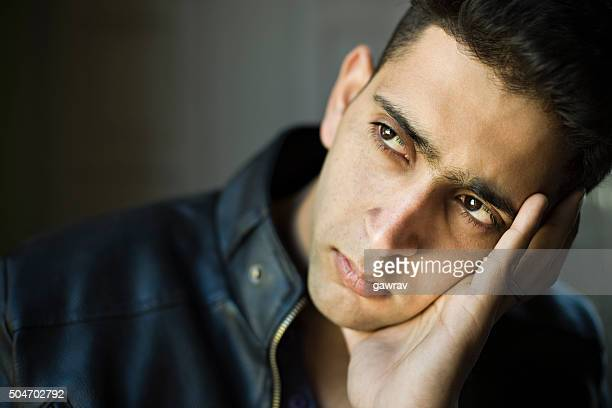 Indoor, serene young man resting head on hand and thinking.