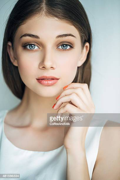 Indoor shot of young beautiful woman on light background