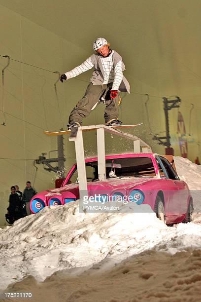 Indoor snowboarder railsliding over a car Snowdome Milton keynes UK 2000's
