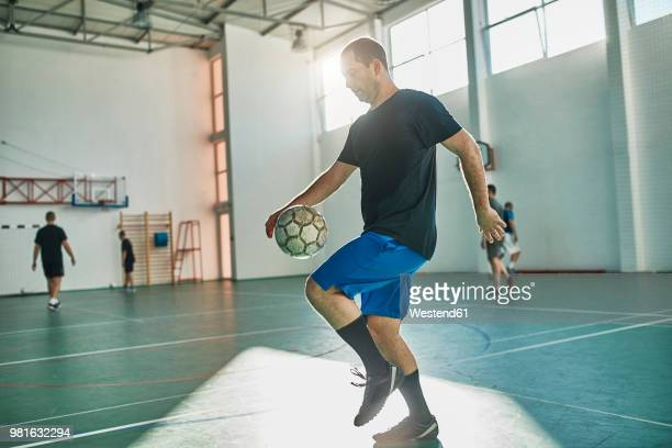 indoor soccer player balancing the ball - cinq personnes photos et images de collection