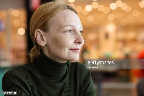 portrait à l'intérieur d'une femme rousse de 45 ans avec des taches de rousseur - une seule femme d'âge mûr photos et images de collection