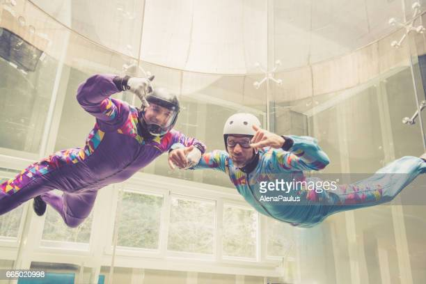 Indoors skydiving -instructor teaching how to fly - freefall simulation - posing
