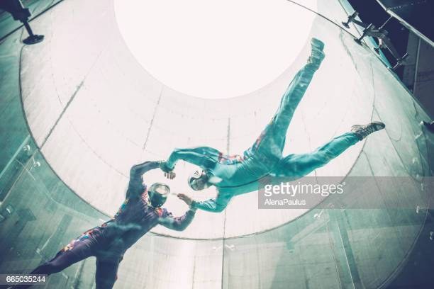 Indoors skydiving -instructor teaching how to fly - freefall simulation