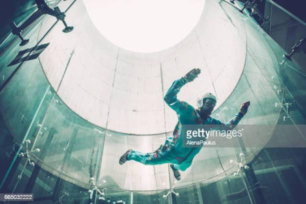 dentro de casa, para-quedismo - um jovem praticar simulação de queda livre - túnel estrutura feita pelo homem - fotografias e filmes do acervo