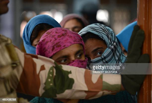 IndoTibetan Border Police personnel stand guard as Kashmiri voters queue at a polling station in Srinagar on December 14 2014 Indiaadministered...