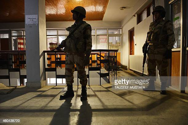 IndoTibetan Border Police personnel stand guard at a polling station in Srinagar on December 14 2014 Indiaadministered Kashmir headed to the Fourth...