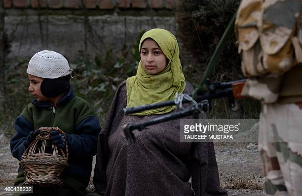 IndoTibetan Border Police personnel stands guard as children warm themselves at a polling station in Srinagar on December 14 2014 Indiaadministered...