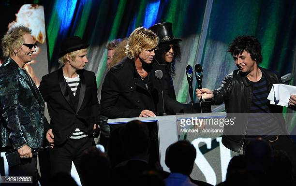 Inductees Matt Sorum Duff McKagan and Slash of Guns N' Roses receive their award from Billie Joe Armstrong and Mike Dirnt of Green Day onstage during...