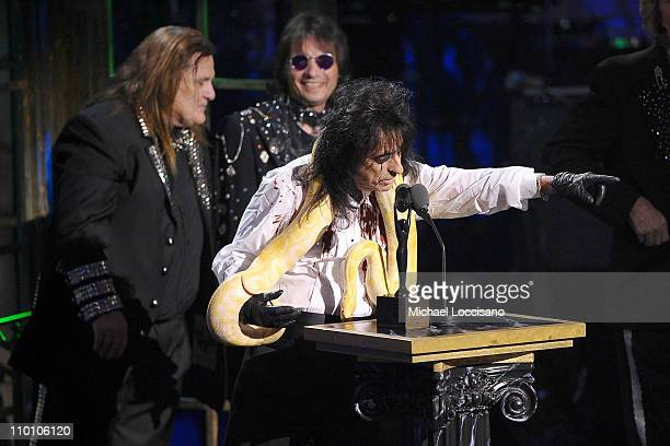 Inductees Michael Bruce Dennis Dunaway and Alice Cooper of Alice Cooper Band pose with a snake and accept their award onstage at the 26th annual Rock...