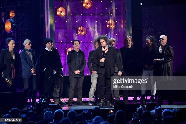 Inductees Pearl Thompson Lol Tolhurst Simon Gallup Robert Smith Jason Cooper Roger O'Donnell and Reeves Gabrels with other members of The Cure speak...