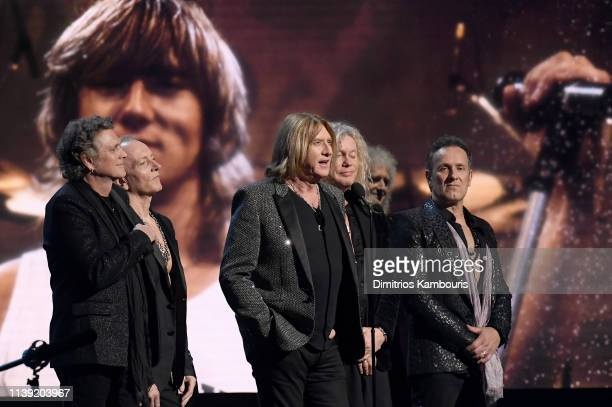Inductees Rick Allen, Phil Collen, Joe Elliott, Rick Savage and Vivian Campbell of Def Leppard and Queen's Brian May speak onstage during the 2019...