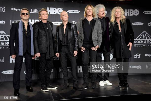 Inductees Vivian Campbell, Rick Allen, Phil Collen, Joe Elliot, and Rick Savage of Def Leppard and Queen's Brian May pose in the press room during...