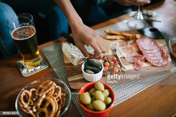 indulging in a charcuterie at a house party - charcuteria fotografías e imágenes de stock