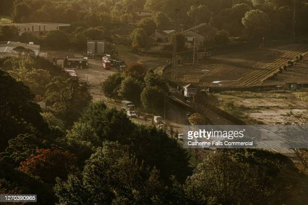 industrial area with a tree lined road, factories and haulage trucks pass through - falls road stock pictures, royalty-free photos & images