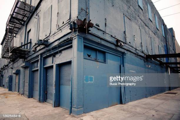 industrial brick building with fire escapes, boarded up windows and metal grates in the meatpacking district, manhattan, new york city - corner stock pictures, royalty-free photos & images