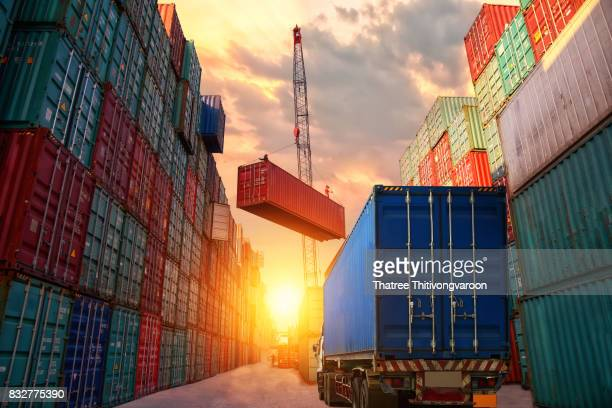 industrial crane loading containers in a cargo freight ship to truck for logistic import export concept details - container stockfoto's en -beelden