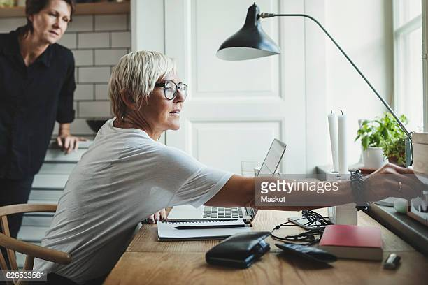 Industrial designer adjusting radio while colleague standing in background at home office