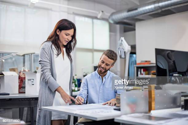 Industrial designer discussing project with coworker