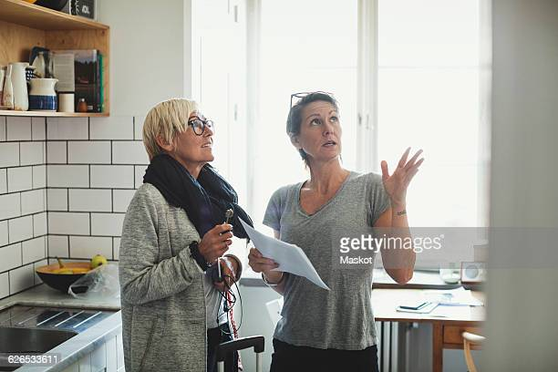 Industrial designer explaining project to colleague at domestic kitchen