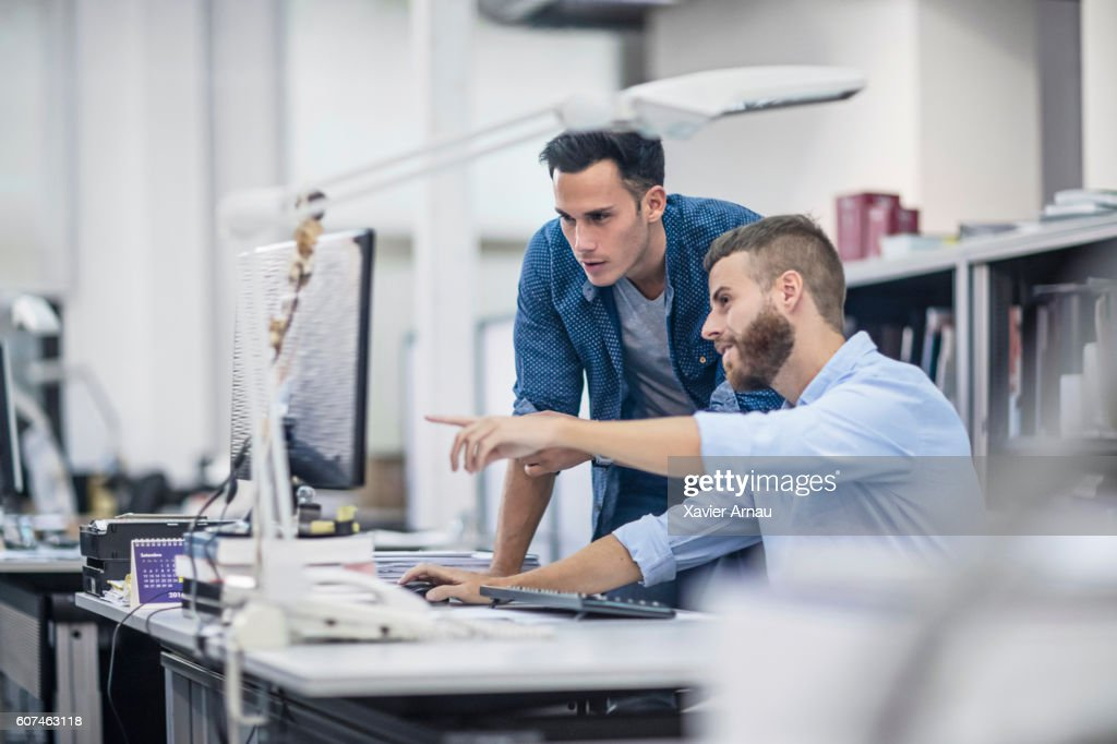 Industrial designers at the office discussing project on the computer : Stock Photo