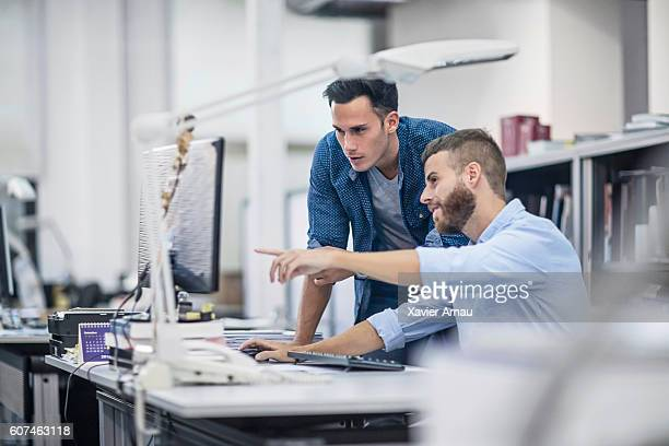 industrial designers at the office discussing project on the computer - guidance stock pictures, royalty-free photos & images