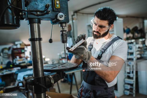 industrieingenieur an der drehmaschine - industrieberuf stock-fotos und bilder
