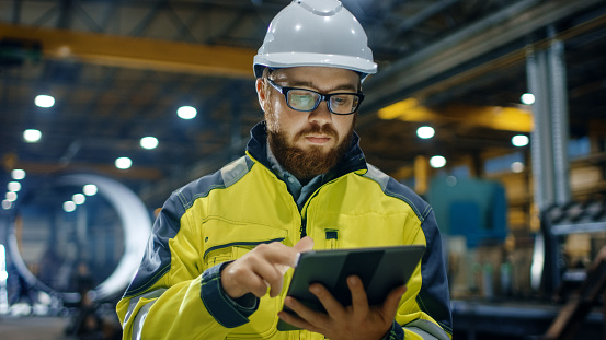 Industrial Engineer in Hard Hat Wearing Safety Jacket Uses Touchscreen Tablet Computer. He Works at the Heavy Industry Manufacturing Factory. 879814122