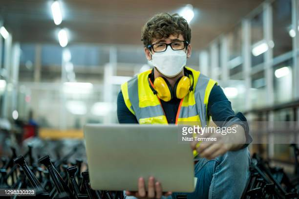 industrial engineer inspecting engineering product by quality check process on laptop in production process. - protective workwear stock pictures, royalty-free photos & images