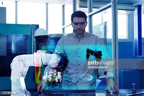 industrial engineer works on the personal computer designing tool part in 3d, using robot . - rechnerunterstützte fertigung stock-fotos und bilder
