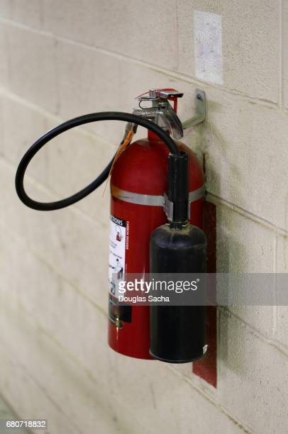 industrial fire extingisher hanging on the wall - 消火器 ストックフォトと画像