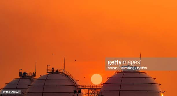 industrial gas storage tank on orange sunset sky. lng or liquefied natural gas storage tank. - 液化天然ガス ストックフォトと画像